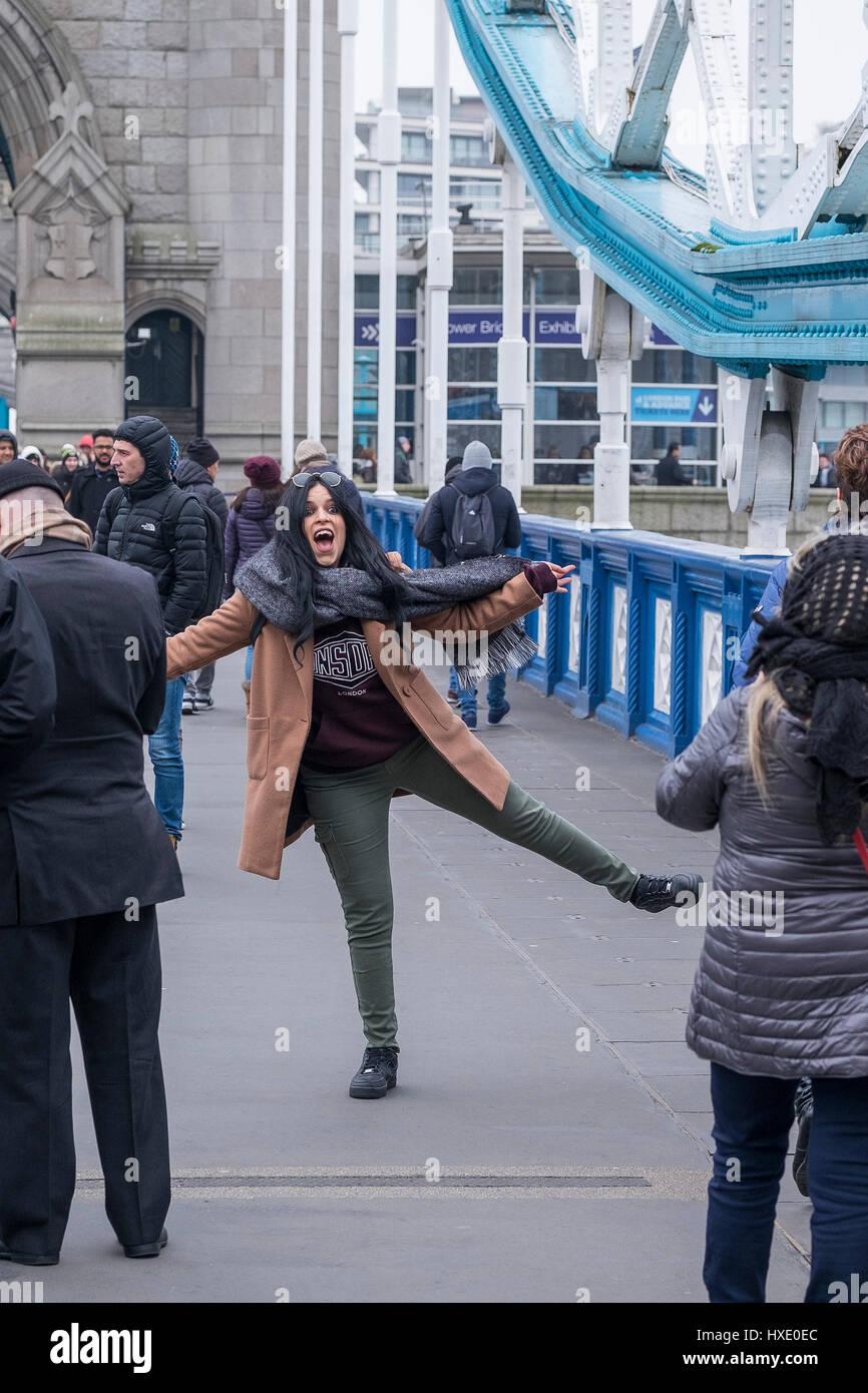 Turista posando para una fotografía en el Tower Bridge de Londres. Imagen De Stock