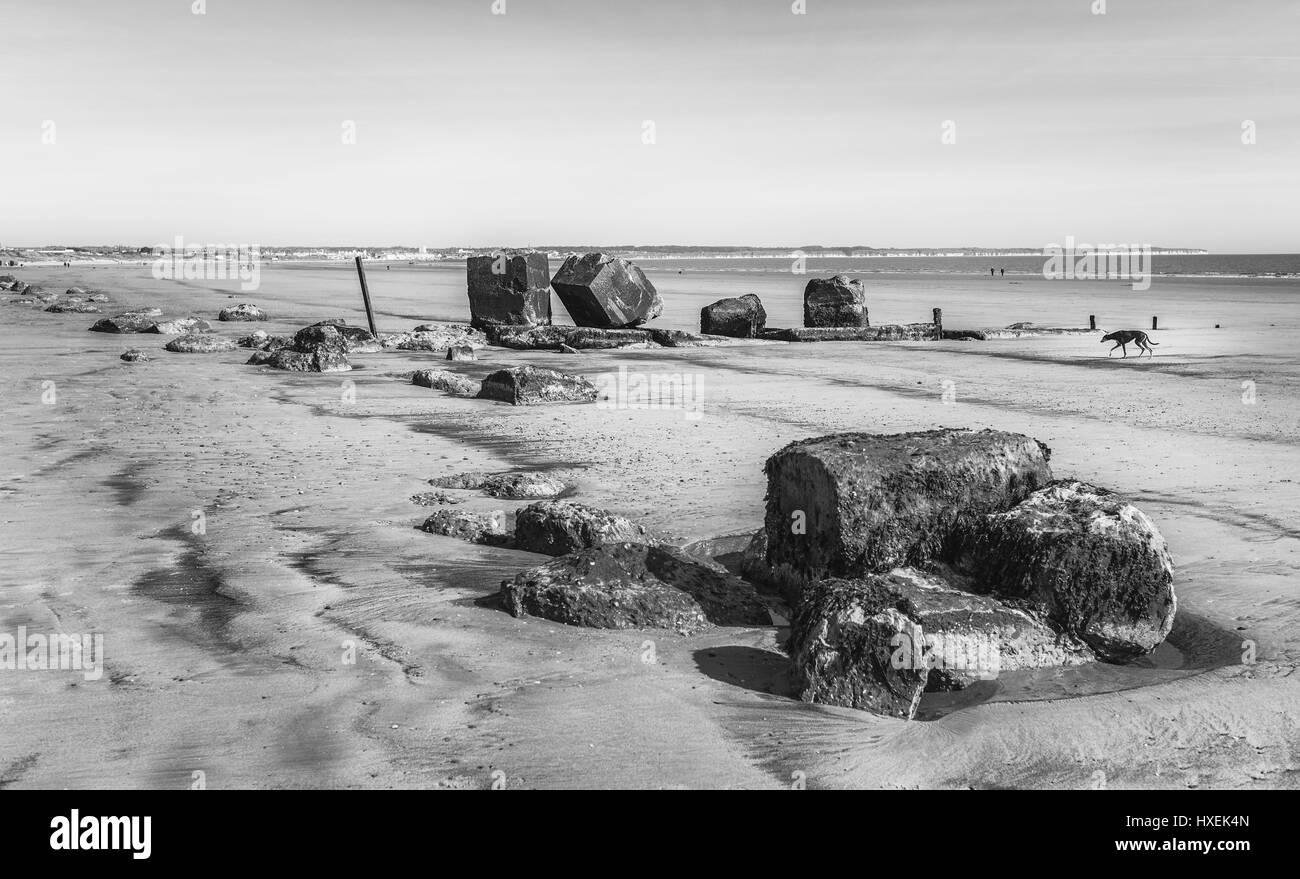 Viejas defensas contra el mar a lo largo de la playa de arena durante la marea baja en una buena mañana de primavera Foto de stock