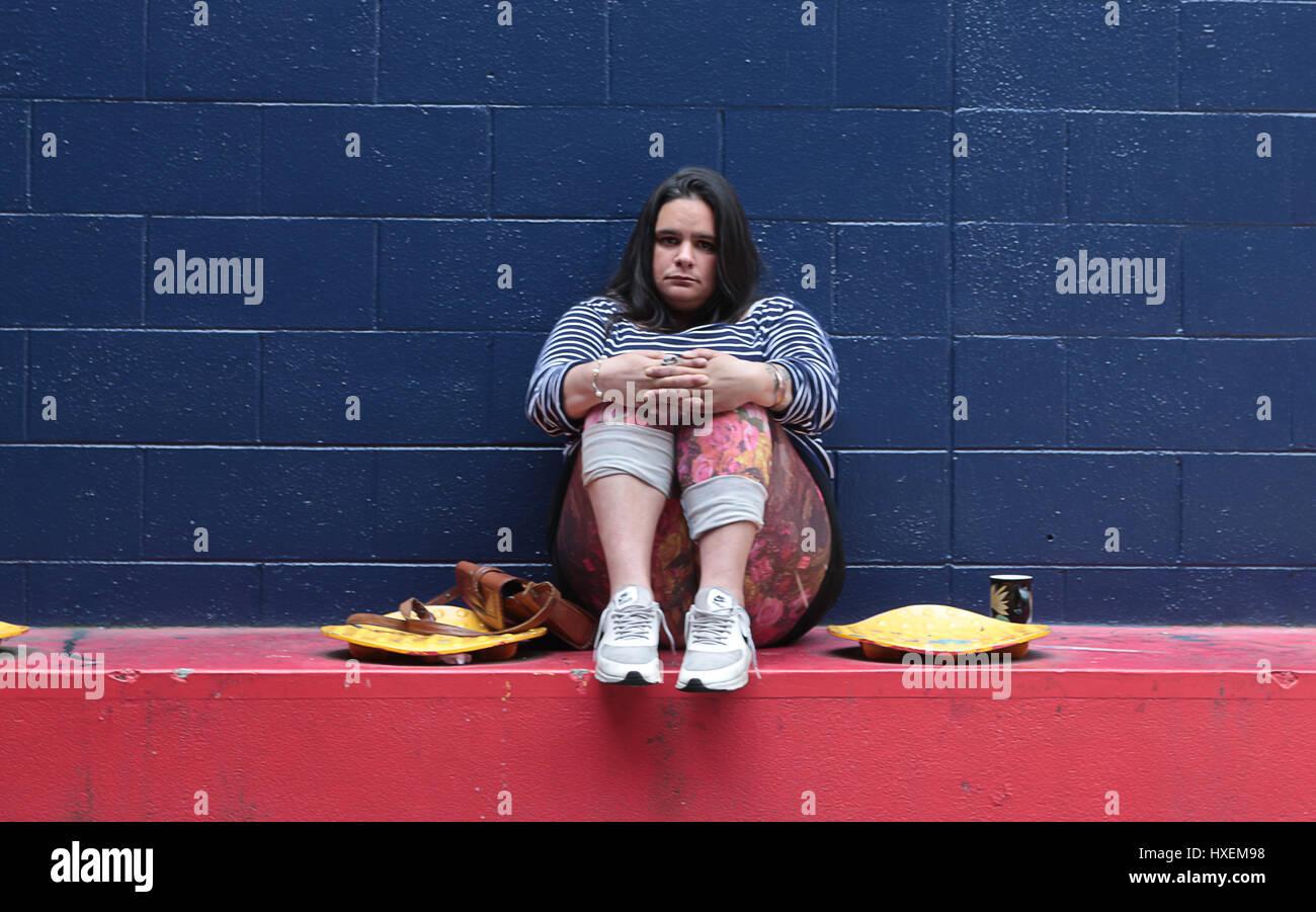 Wellington, Nueva Zelanda - 10 de febrero de 2017: Una mujer sentada en una pared azul fuera de un edificio mirando Imagen De Stock