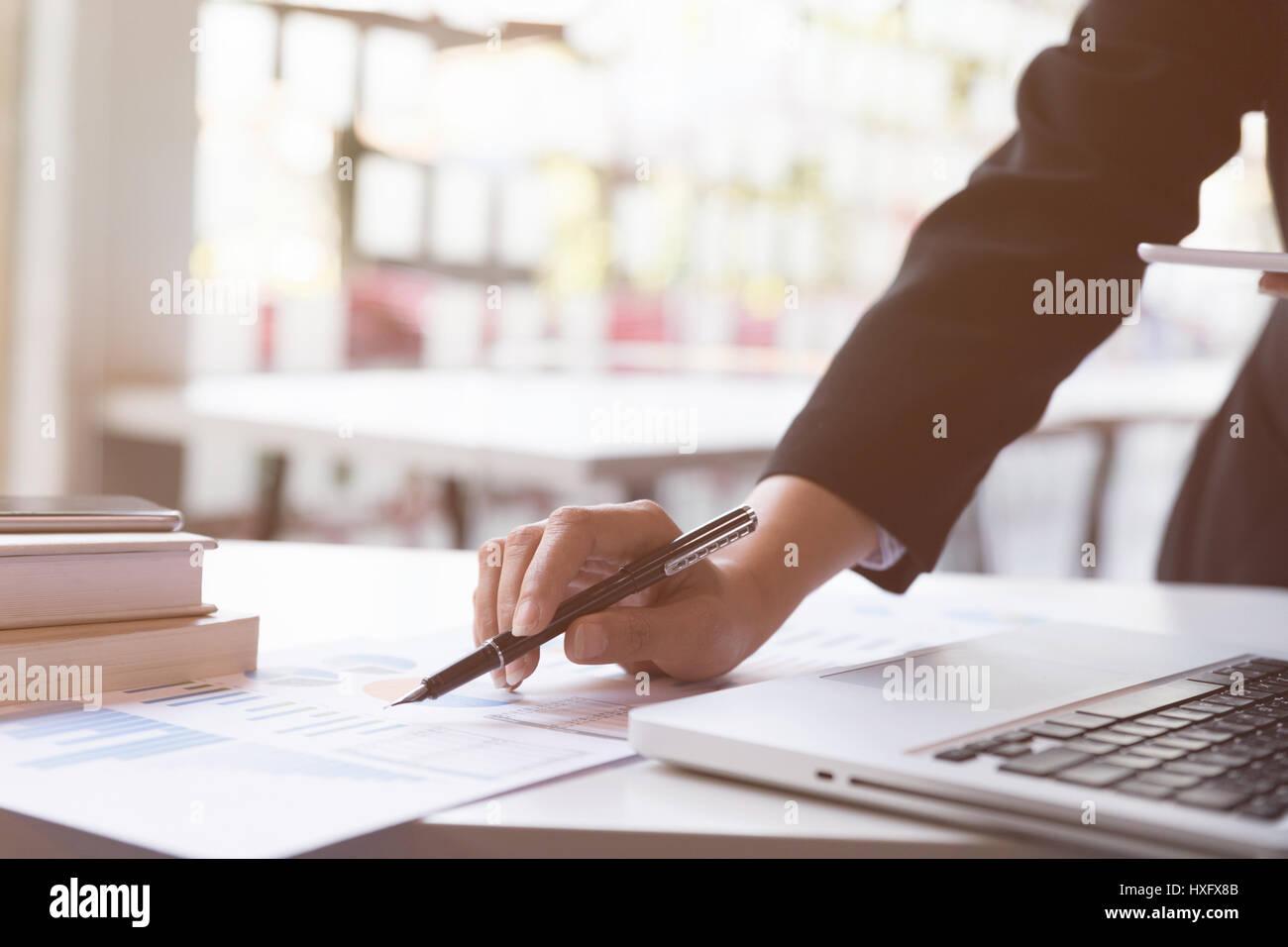 Mujer trabajadora mano sosteniendo pen con resumen de Negocio o Business Plan informe con gráficos y diagramas Imagen De Stock