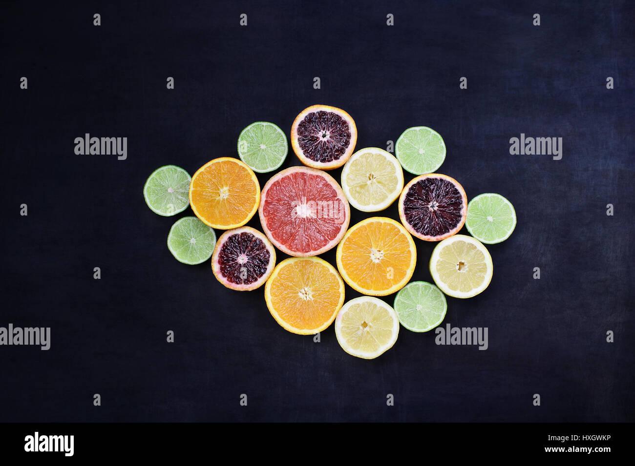 Variedad de frutas cítricas (naranja, sangre, naranjas, limones, pomelos y limas) sobre un fondo negro de estilo Foto de stock