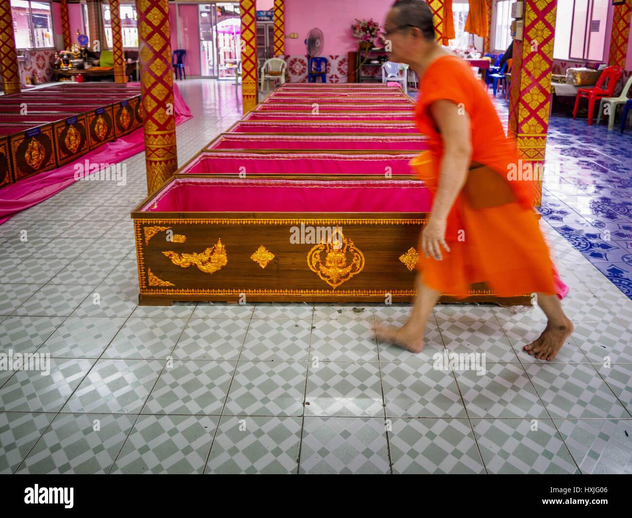 Bang Kruai, Nonthaburi, Tailandia. 29 Mar, 2017. Un monje budista camina pasado una fila de ataúdes después Imagen De Stock