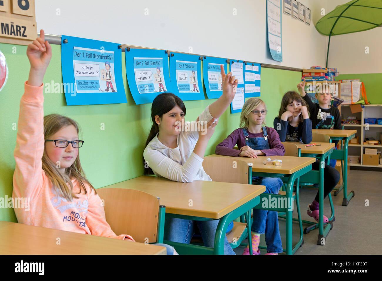 Los niños levantando sus manos en la escuela primaria Imagen De Stock