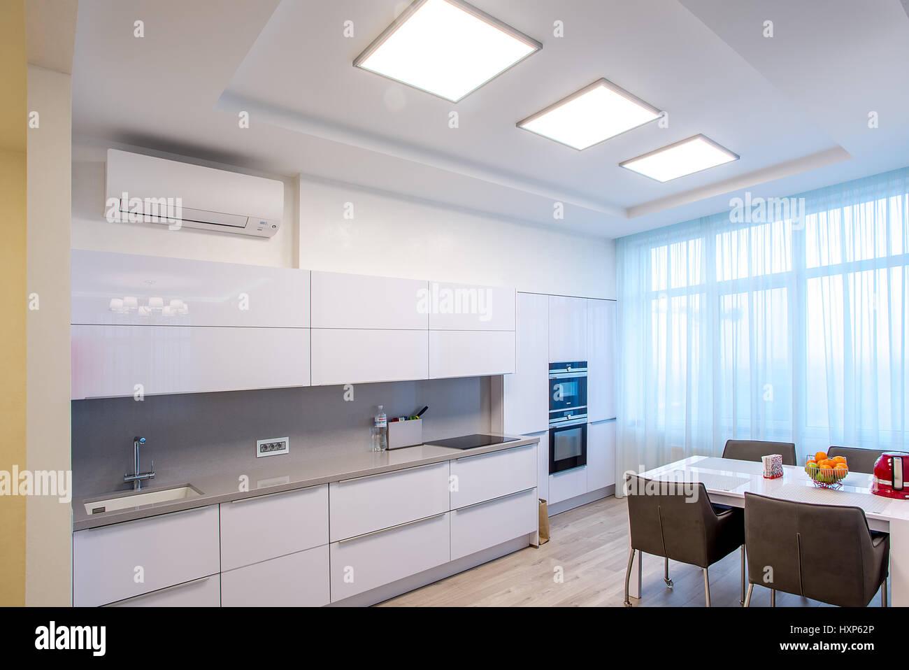 Cocina blanca con mesa y grandes ventanales Foto & Imagen De Stock ...