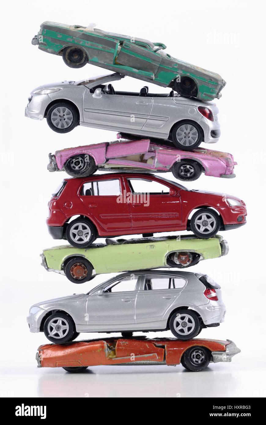 Roto y apiladas nuevos automóviles en miniatura, el estancamiento de las nuevas ventas de carro al final de la caja, Kaputte clunkers und neue gestapelte Miniaturautos, sto Foto de stock
