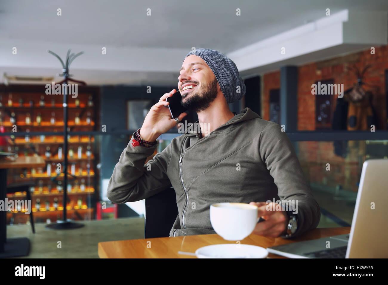 Joven apuesto hipster hombre con barba sentado en la cafetería hablando de teléfonos móviles, sosteniendo Imagen De Stock