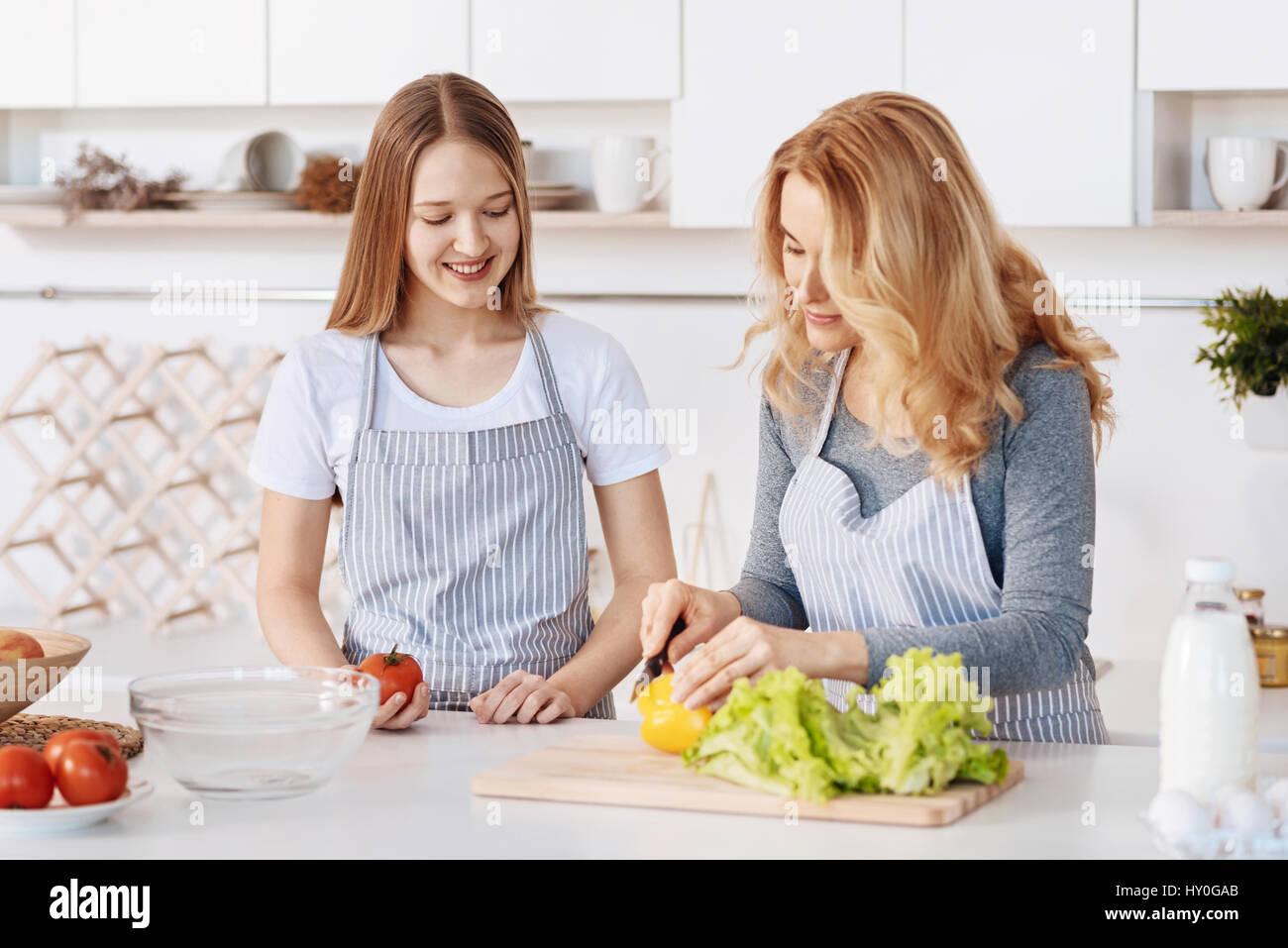 Cada día la lección. Agradable amorosa Madre de pie en la cocina con su hija mientras cocinan juntos Imagen De Stock
