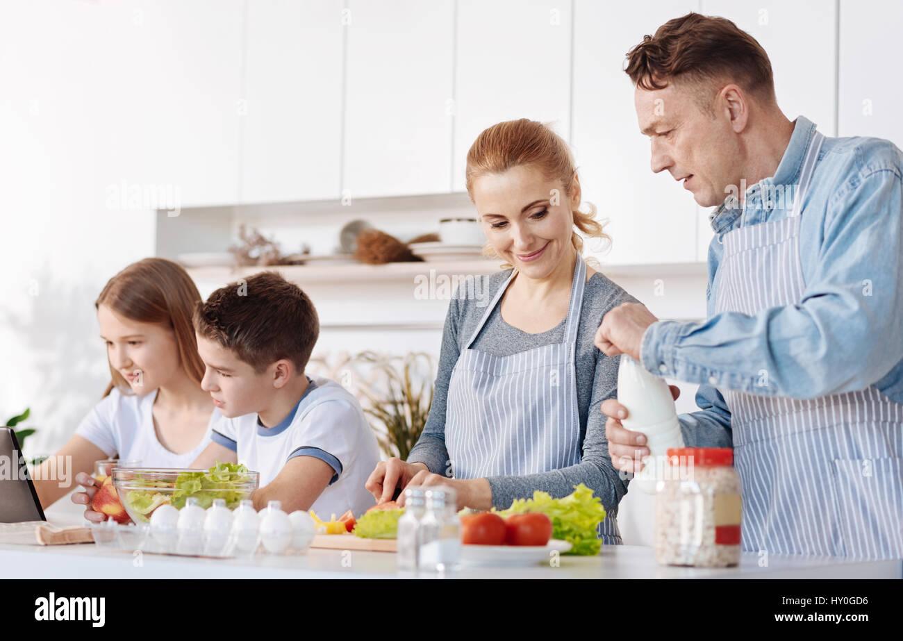 Siga la receta. Alegre ambiente familiar cada día para cocinar la cena juntos mientras está de pie en Imagen De Stock