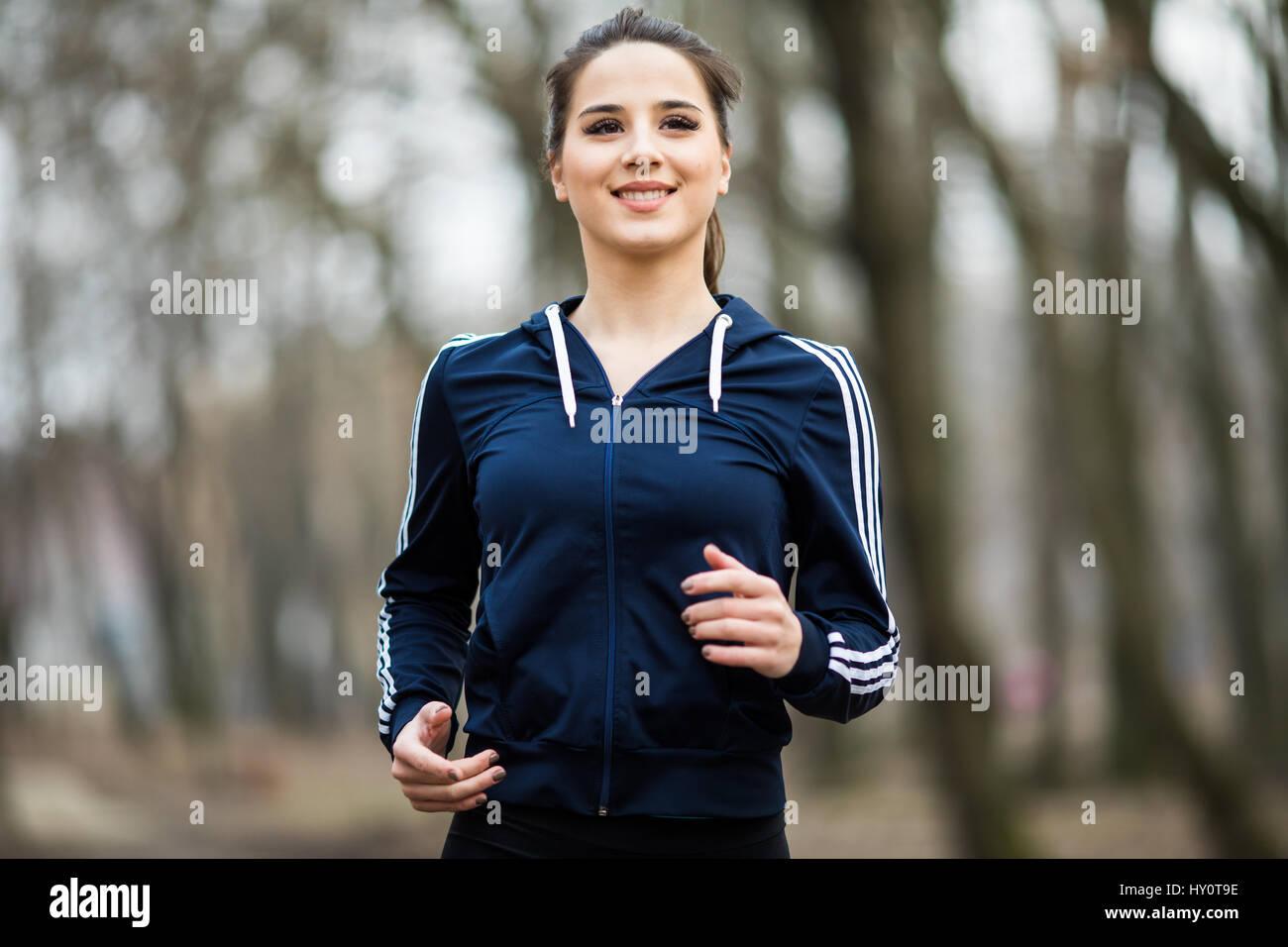 Mujer joven en funcionamiento y formación en otoño la naturaleza Imagen De Stock