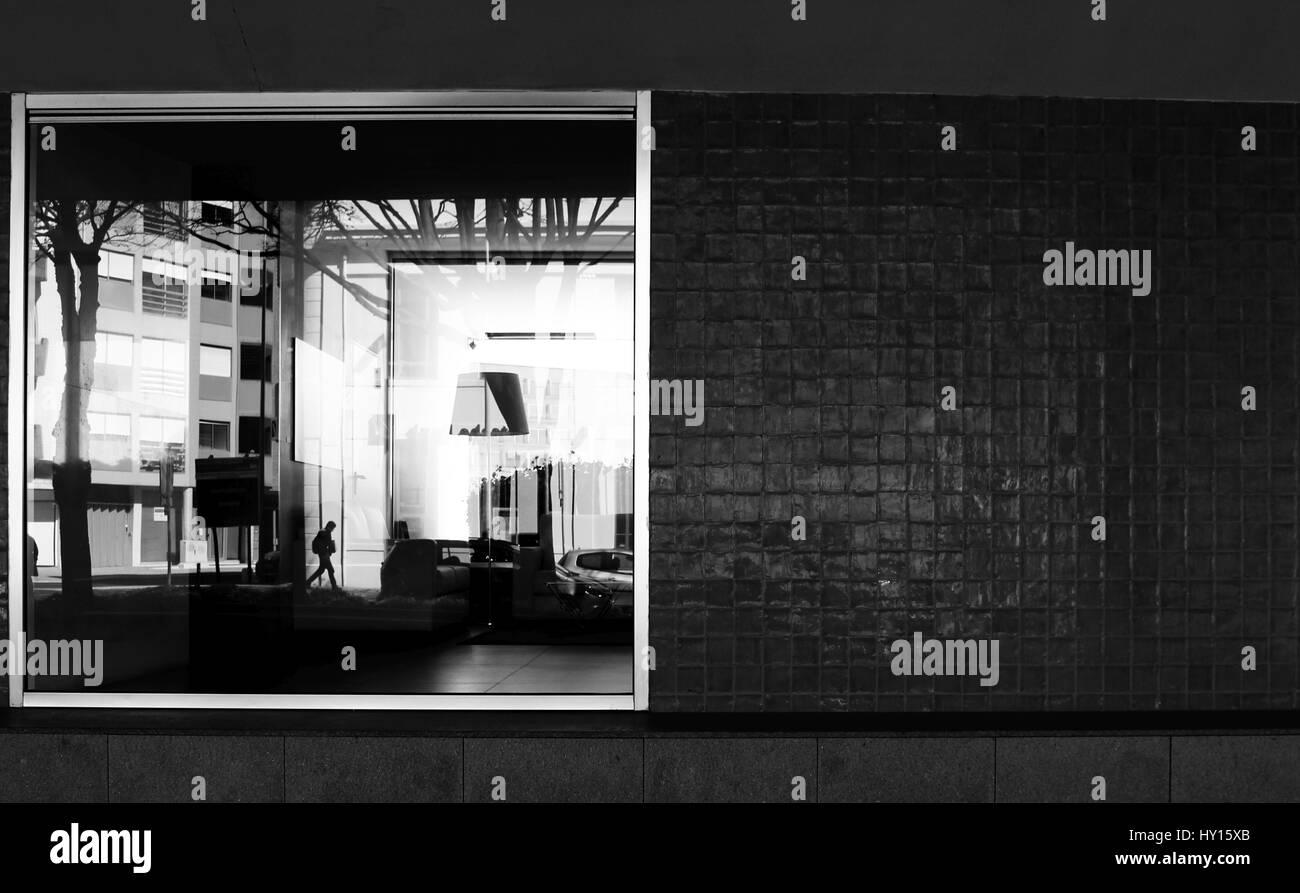 La ventana de un edificio donde se puede ver un poco de su interior, así como el reflejo de todo lo que está pasando Foto de stock