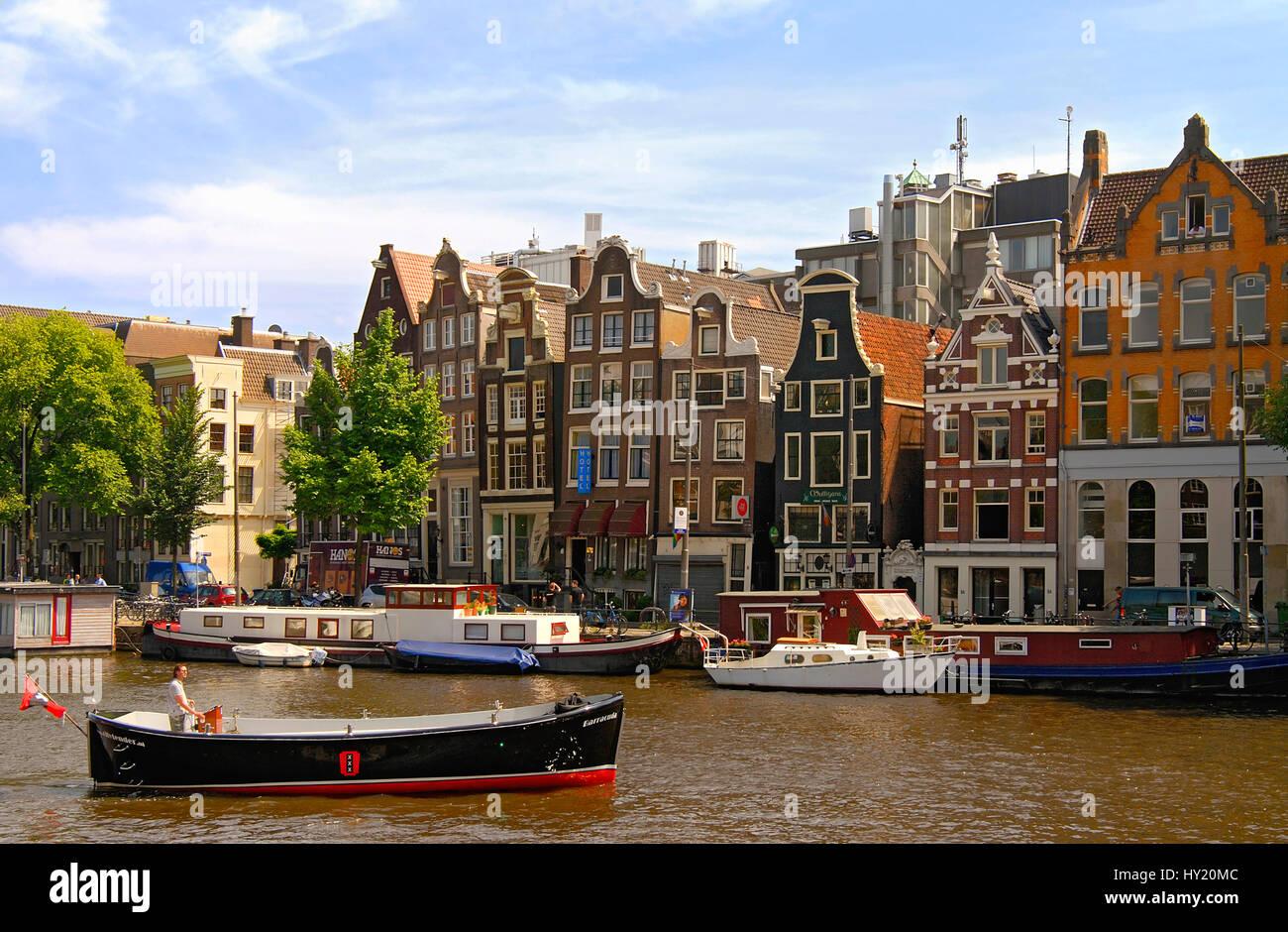 Imagen de pequeño barco de motor la conducción en un canal de agua en el interior de la ciudad de Amsterdam, Holanda. Foto de stock