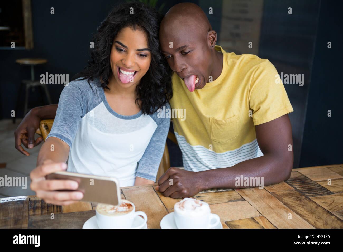 Juguetón pareja haciendo caras mientras toma selfie en la cafetería. Imagen De Stock