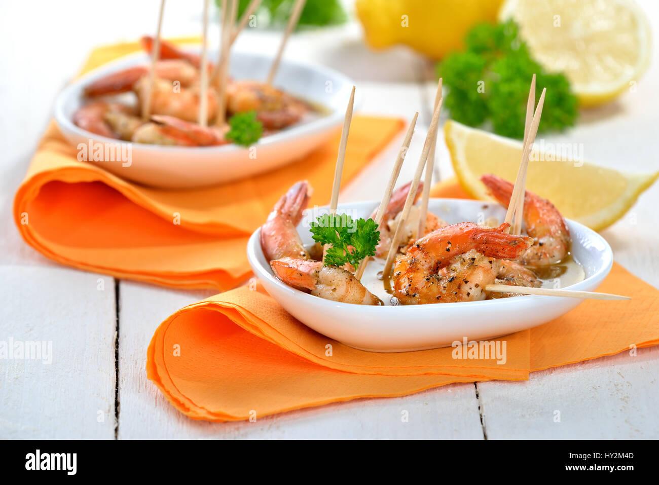 Las tapas españolas - picante de langostinos fritos con aceite de oliva, Jerez y ajo. Foto de stock
