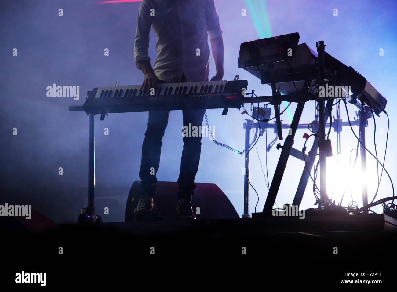 Disco jokey mezclar en el escenario más iluminada de fondo de humo Foto de stock