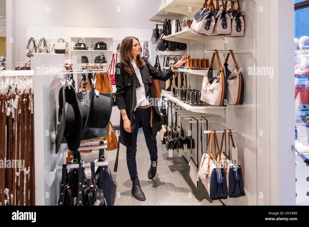 Suecia, mujer elegir el bolso en la tienda Imagen De Stock