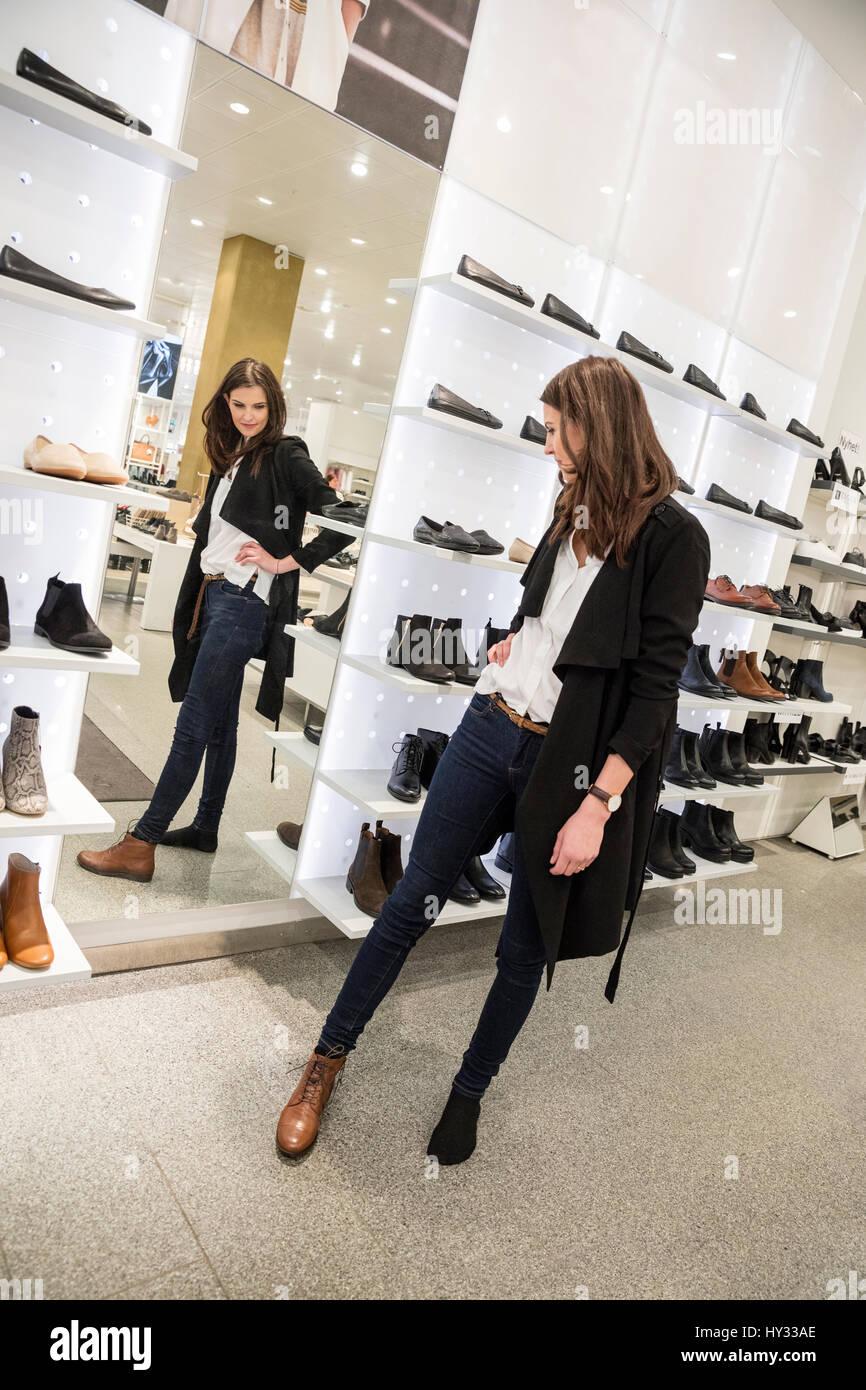 Suecia, mujer escoger zapatos en la tienda Imagen De Stock