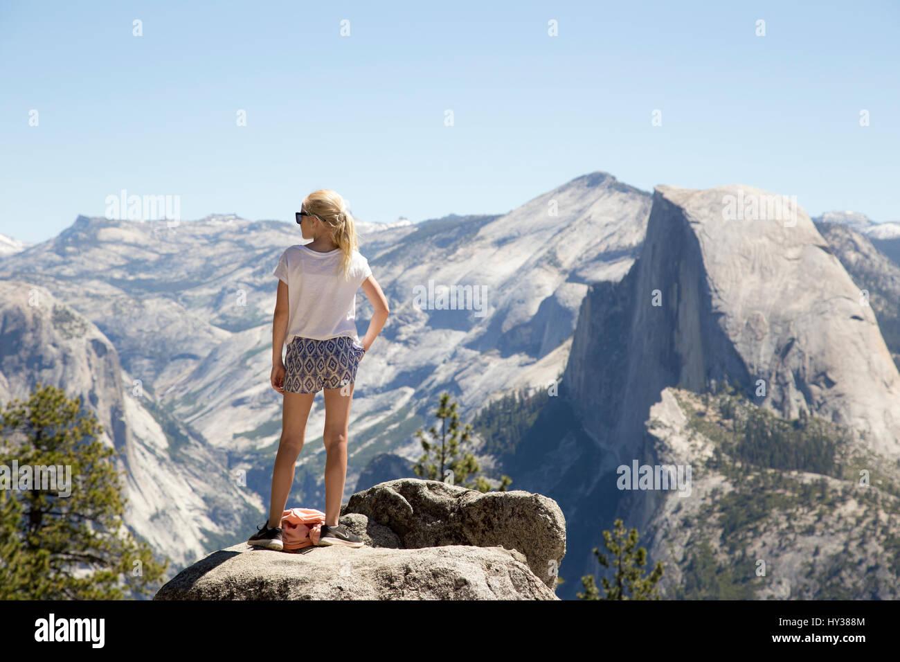 California, Estados Unidos, Yosemite, Chica (12-13) mirando a ver con Sentinel Dome y cataratas de Yosemite Foto de stock