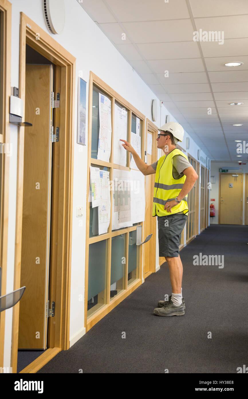 Suecia, hombre ropa de pie en el pasillo y apuntando sobre papeles colgados en la pared Imagen De Stock