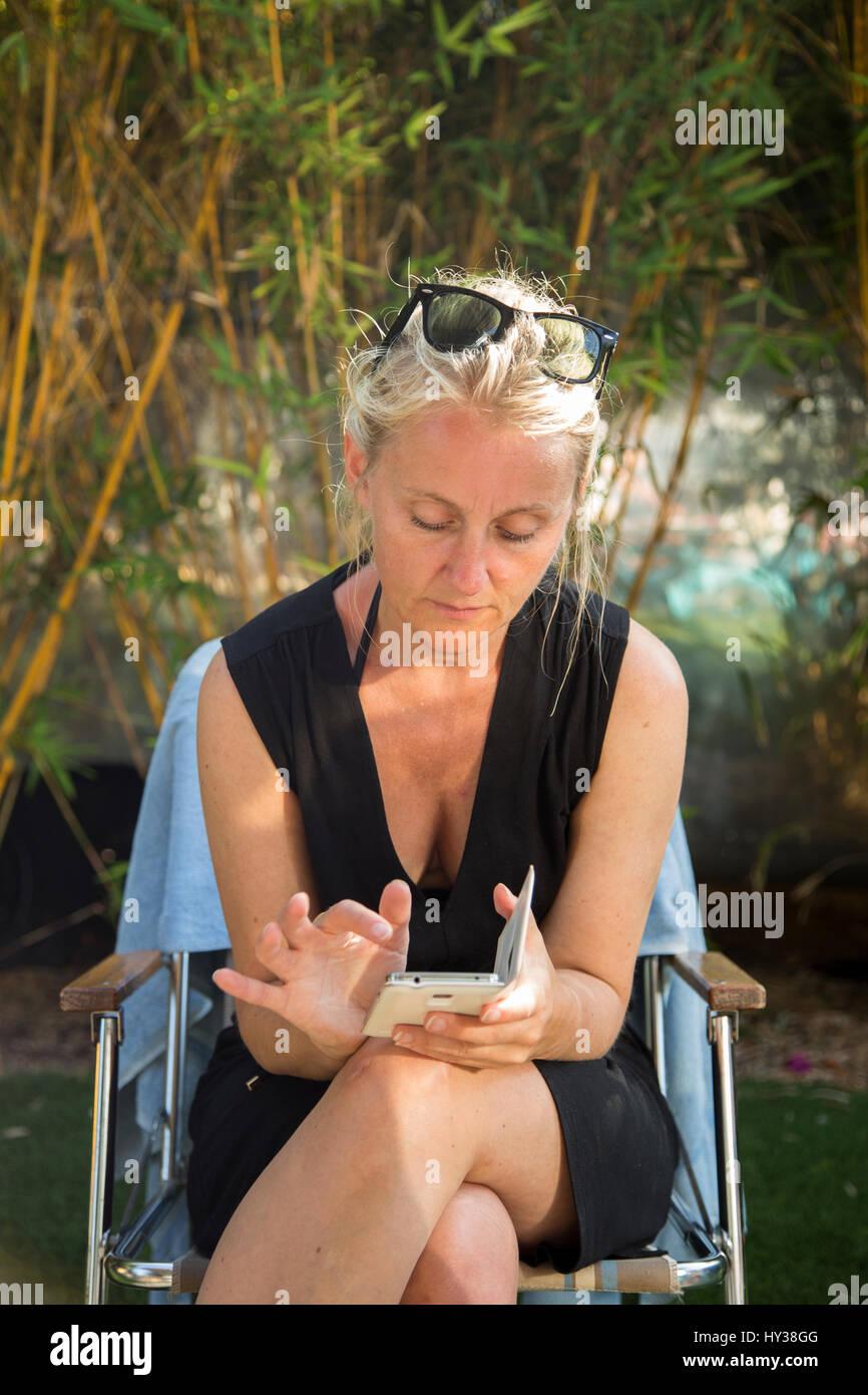 California, Estados Unidos, Santa Bárbara, mujer madura, sentada en la silla al aire libre y el uso de teléfono Foto de stock