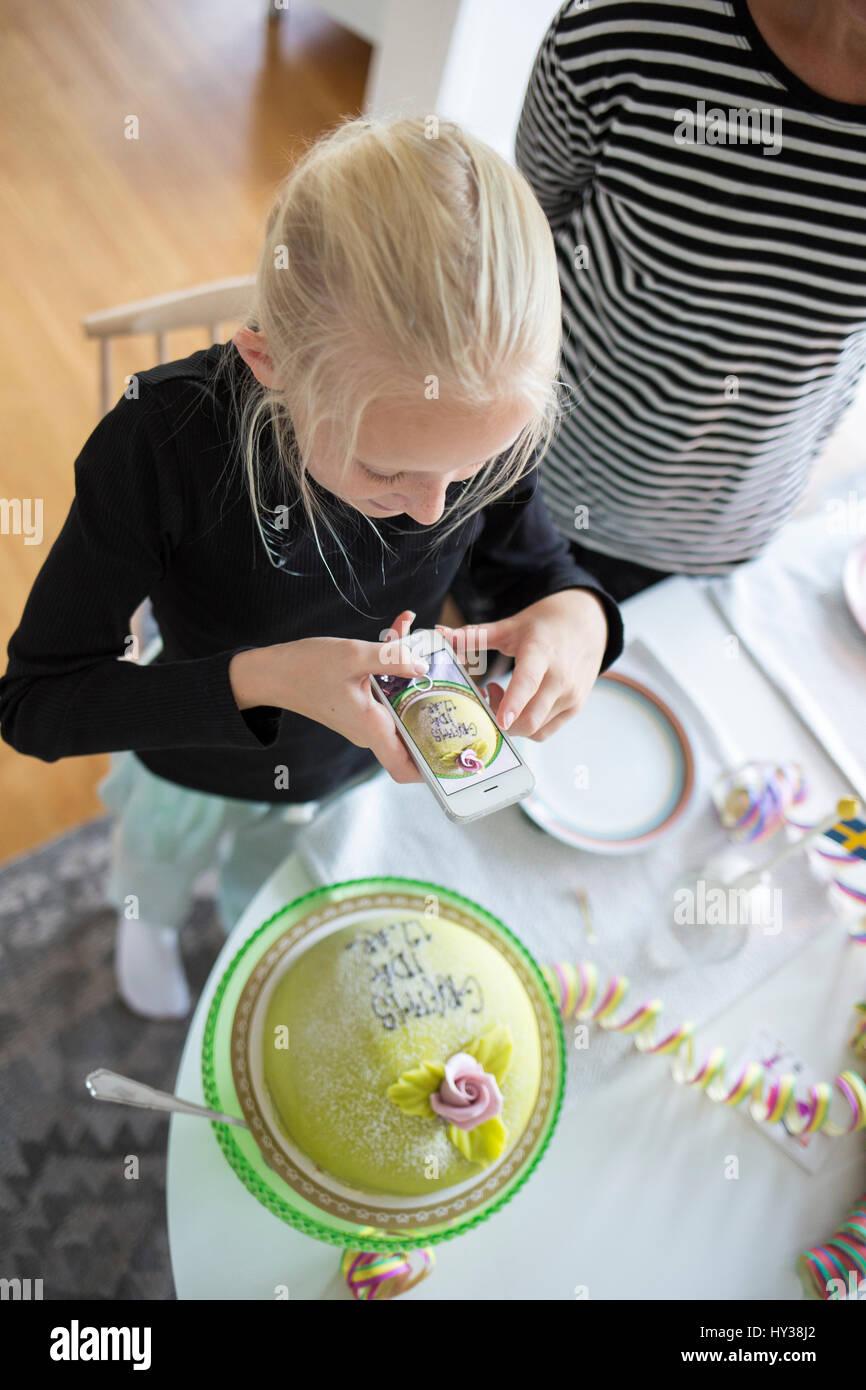 Suecia, chica (12-13) fotografiando el pastel de cumpleaños con teléfono celular Imagen De Stock