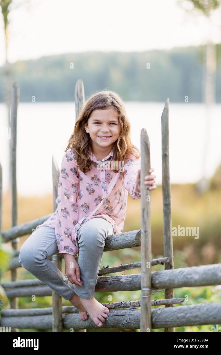 Suecia, vastmanland, hallefors, bergslagen, retrato de niña sonriente ( 8-9) sentados en el cerco Imagen De Stock