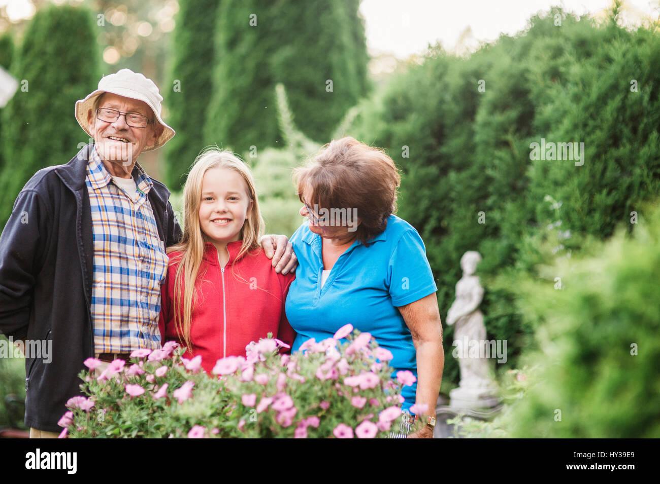 Suecia, vastmanland, hallefors, bergslagen, girl (12-13) con los abuelos posando en el jardín Imagen De Stock