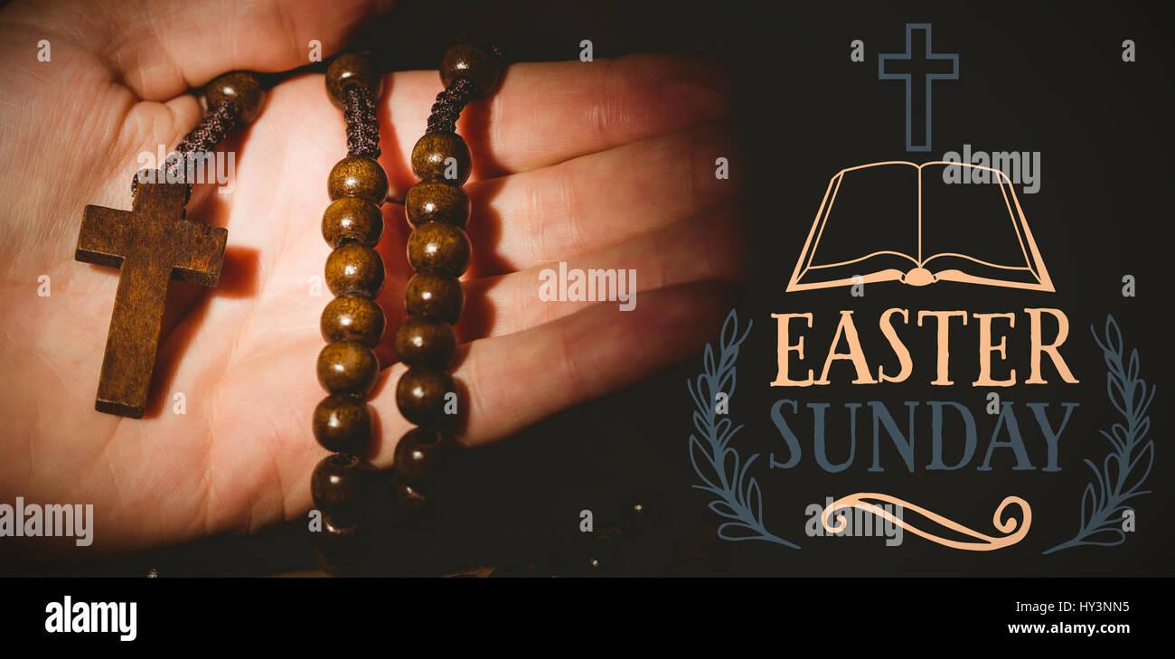 Mensaje de Pascua contra mano sosteniendo Rosario Imagen De Stock