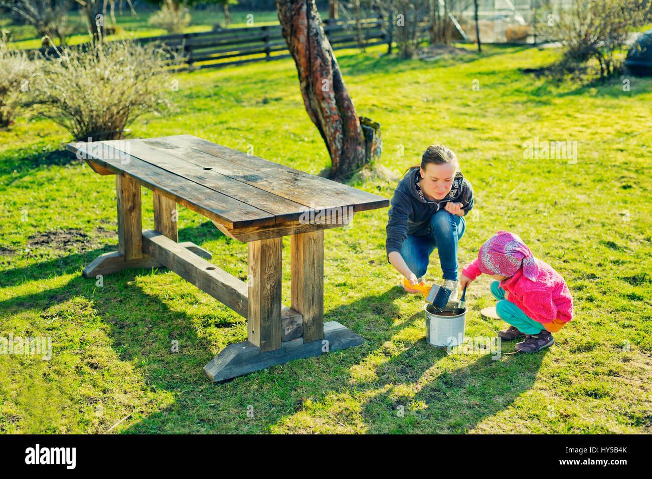 Finlandia, paijat-deshonra, Heinola, Madre Hija (4-5) aceitando mesa de madera en el jardín Imagen De Stock