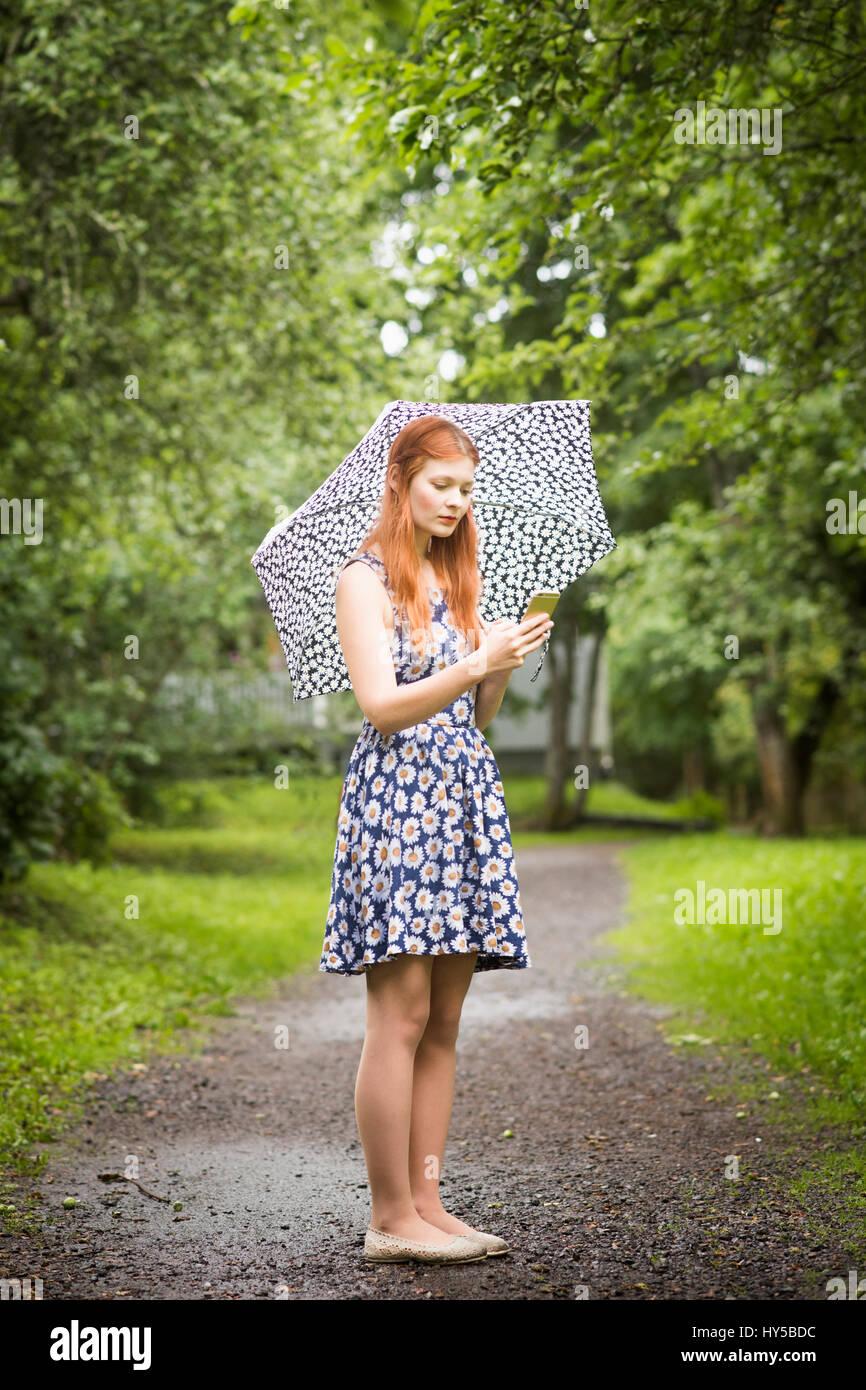 Finlandia, Pirkanmaa, Tampere, mujer vistiendo vestido floral con sombrilla permanente en el parque Imagen De Stock