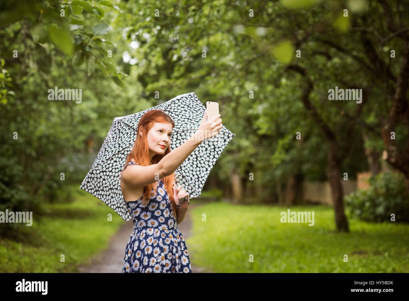 Finlandia, Pirkanmaa, Tampere, mujer vistiendo vestido floral de pie con paraguas en el parque y teniendo selfie Imagen De Stock