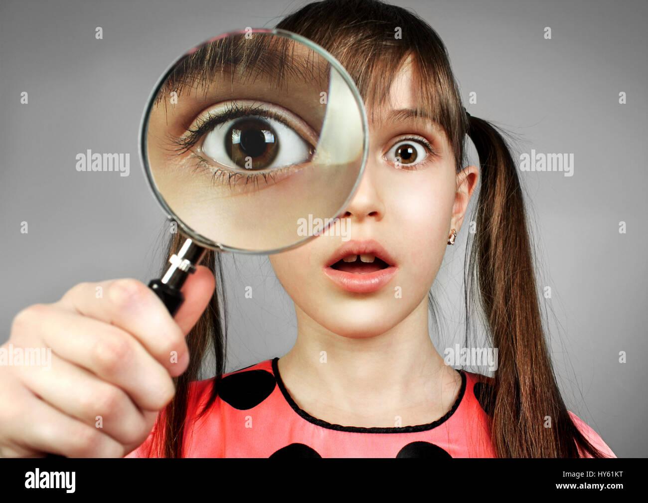 Sorprendido chica, buscando con lupa Imagen De Stock