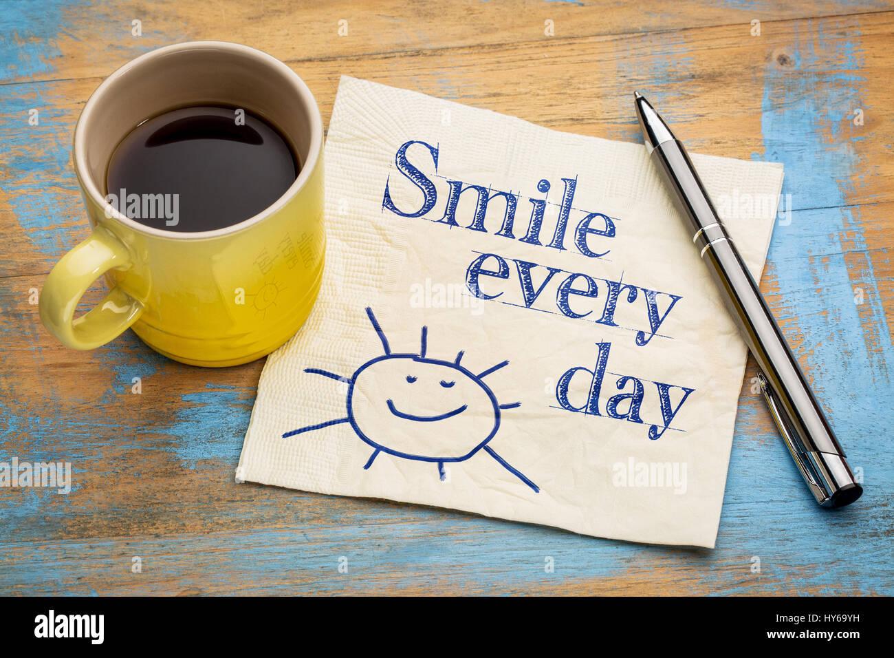 Sonreír cada día - alegre de la escritura a mano en una servilleta con una taza de café espresso Imagen De Stock