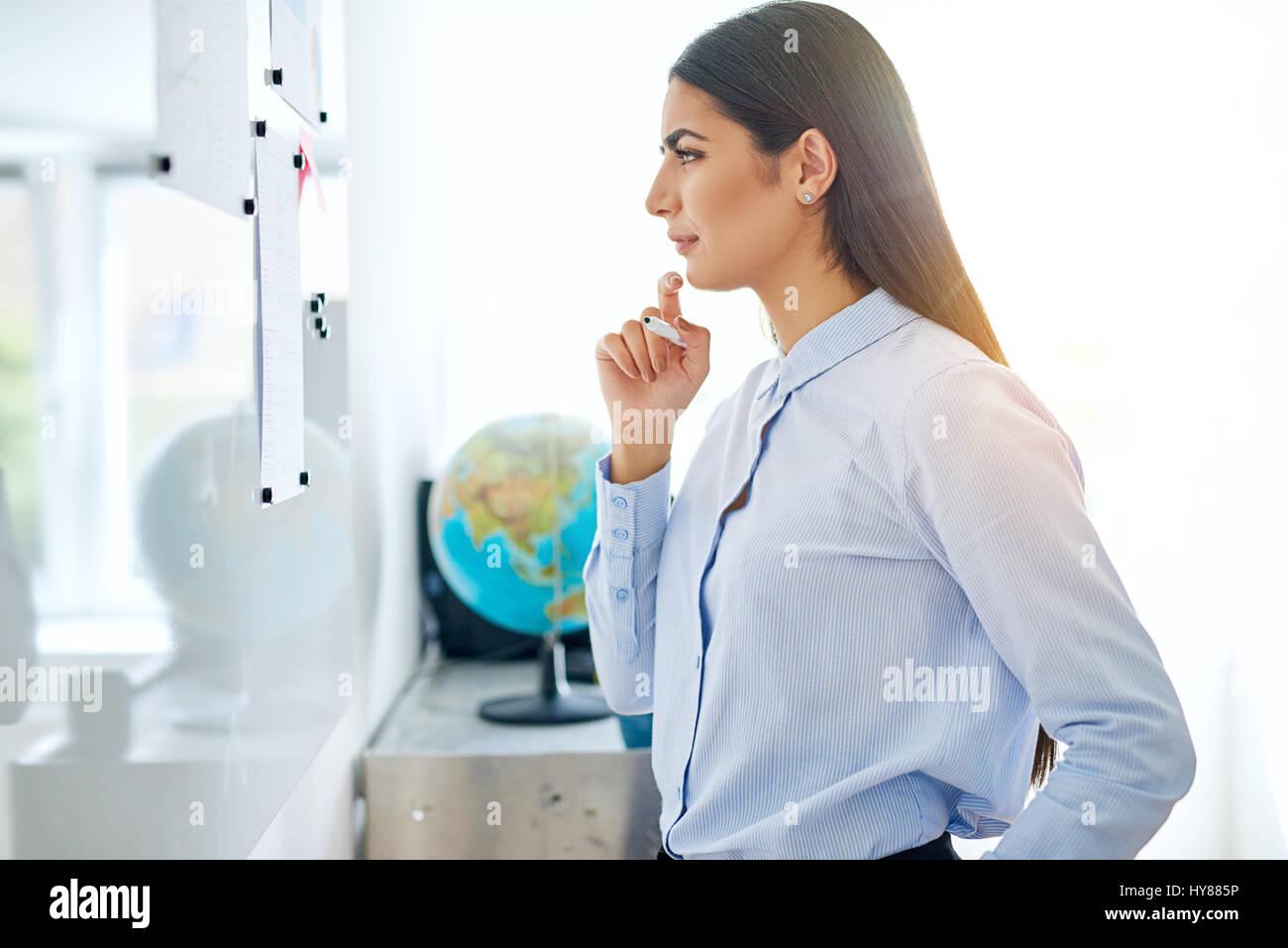 Pensativo empresaria leer un anuncio sobre una placa reflectante con su dedo a su barbilla y una expresión pensativa, Foto de stock