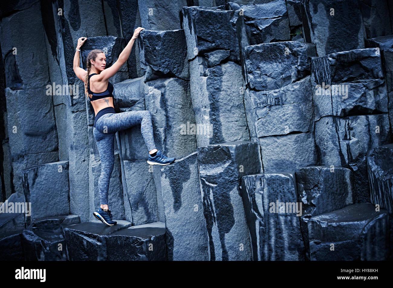 Feliz confía en las mujeres jóvenes la escalada en roca basáltica en el sur de Islandia Foto de stock