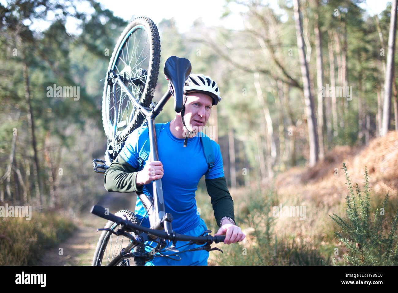 Un hombre lleva su bicicleta de montaña en el bosque Imagen De Stock