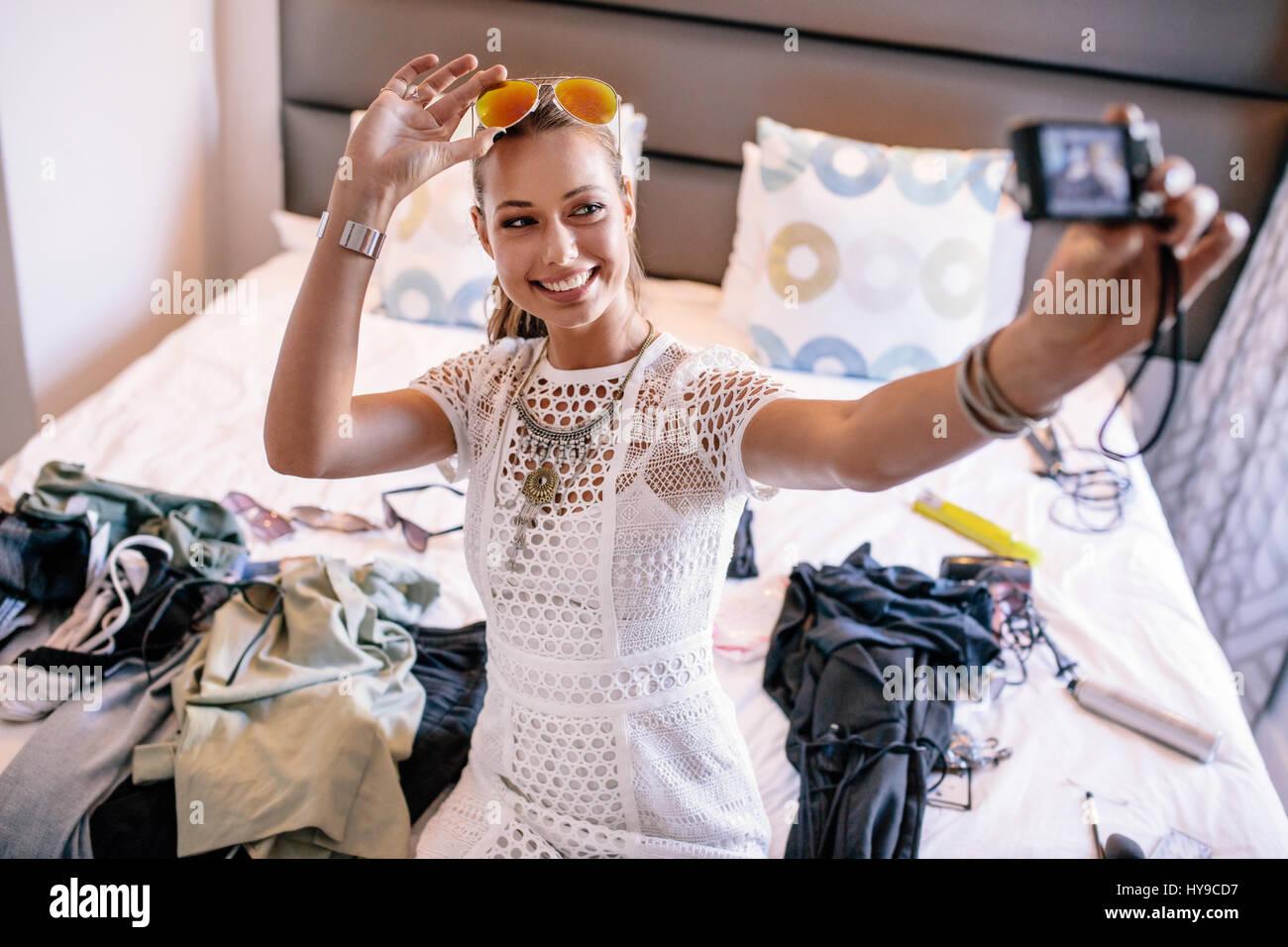 Grabación vlogger hembra broadcast con cámara digital. Una mujer que toma video selfie mostrar ropa de Imagen De Stock