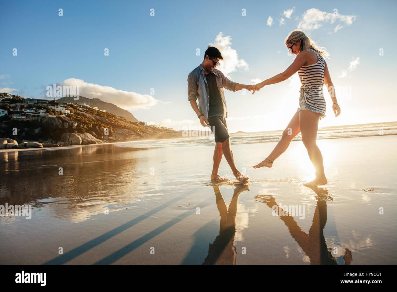 Hermosa joven pareja tomados de las manos y jugando en la orilla. Feliz joven pareja romántica en el amor divirtiéndose Imagen De Stock