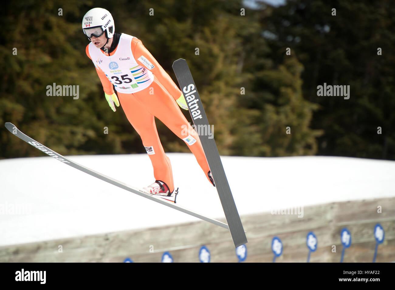 El equipo de Canadá esquí Mackenzie Boyd-Clowes puente vuela fuera de la colina grande saltar en el Whistler Imagen De Stock