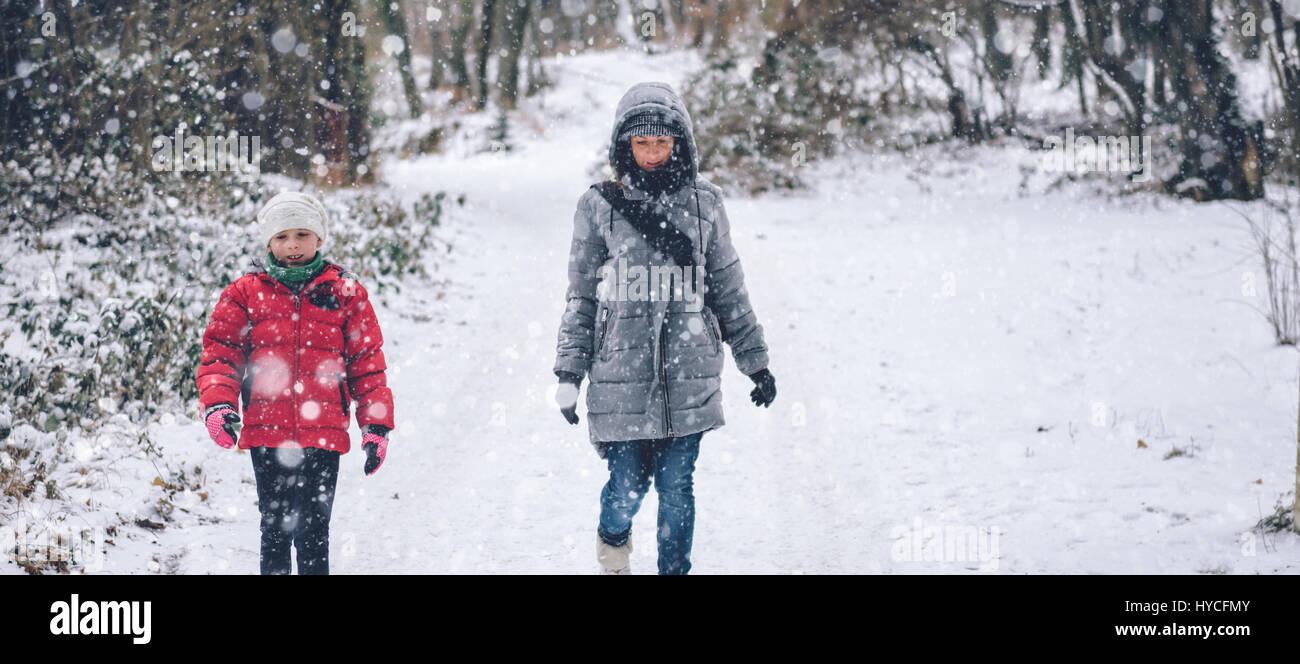 La madre con la hija de senderismo en el bosque de invierno blanco Imagen De Stock
