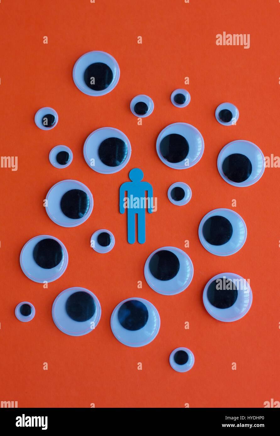 La figura de un hombre rodeado de ojos mirando a él. Imagen De Stock