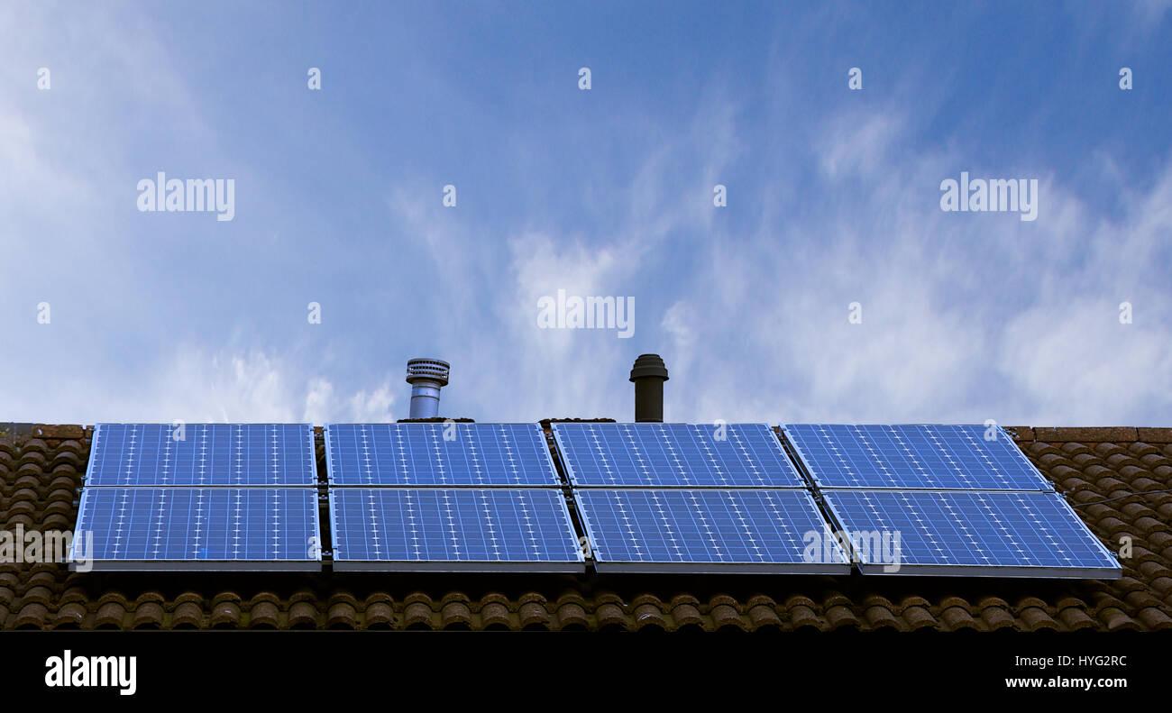 Paneles solares en el tejado inclinado con el cielo azul de fondo, Stoke on Trent, Staffordshire, Reino Unido.La Imagen De Stock