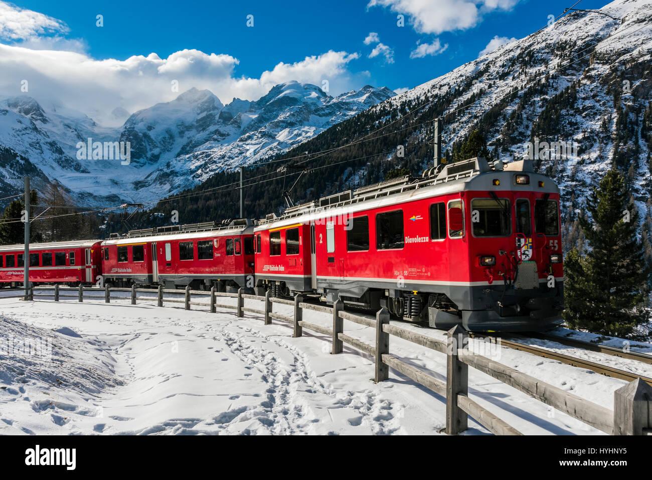 Vista invernal de la Bernina Express tren rojo con Bernina y Glaciar Morteratsch en el fondo, de Graubunden, Suiza Foto de stock