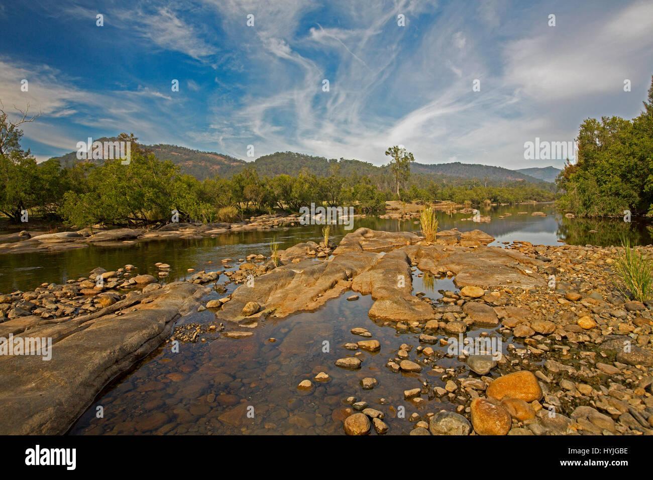 Vista panorámica del curso pedregoso del Río Mann dobladillo con bosques y con rangos en el horizonte Imagen De Stock