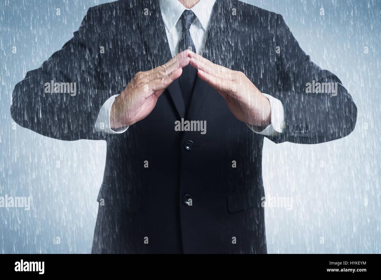 Empresario de palo con las dos manos en posición para proteger en tiempo lluvioso día (centrándose en la mano, Blur Foto de stock
