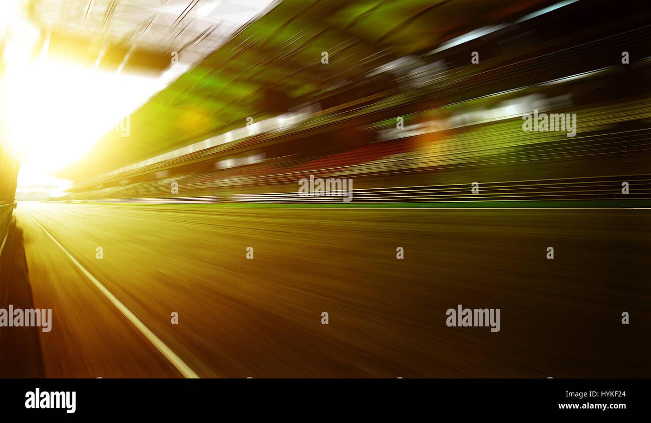 Foward Movimiento Desenfoque de lente, circuito de carreras de velocidad con fondo asentado stand , Sol escena . Imagen De Stock