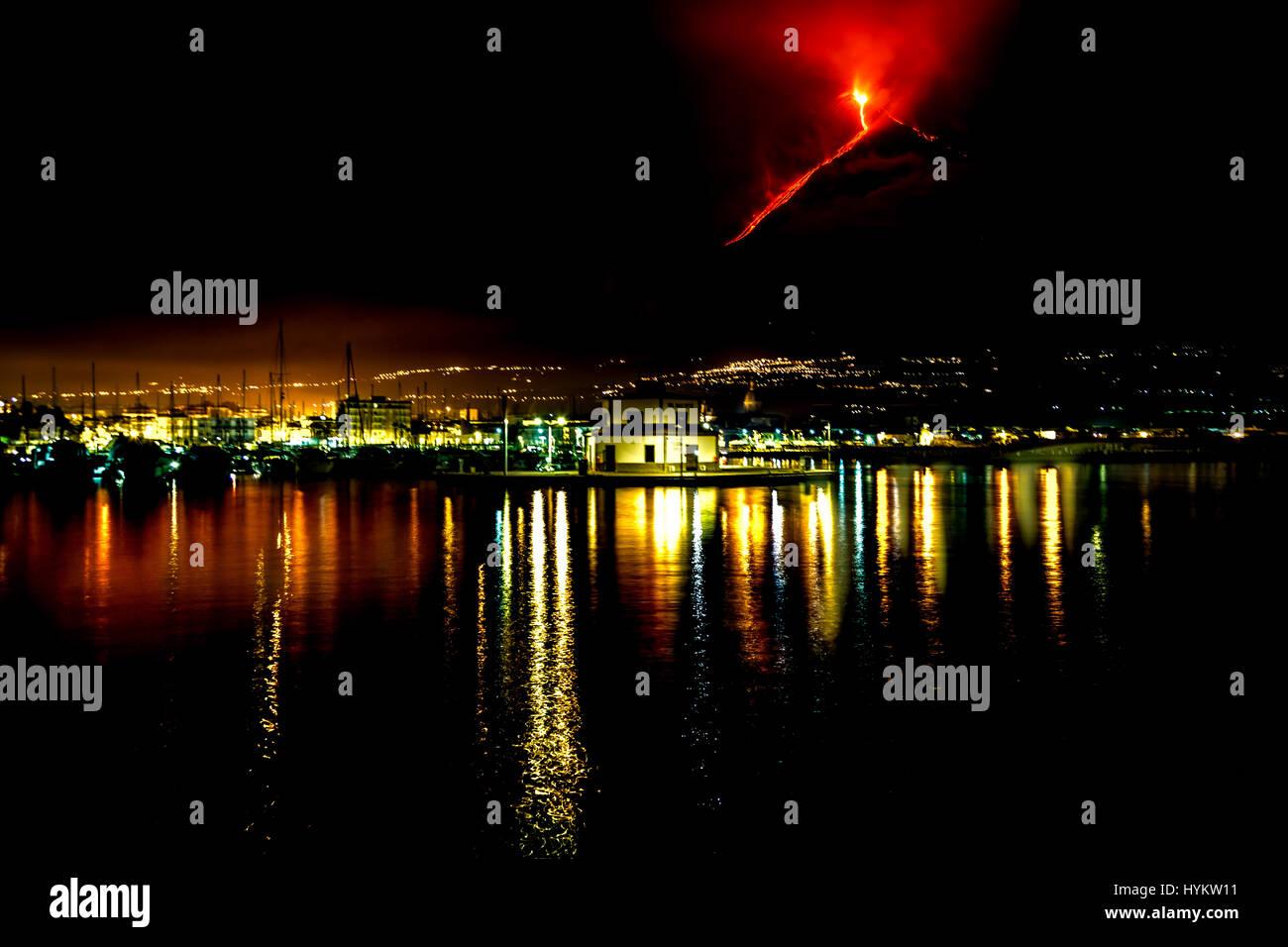 MESSINA, Sicilia: Una imagen nocturna de una erupción en el Monte Etna, tomada desde el puerto Riposto. Un hongo nuclear como cloud voladura del Monte Etna, en Sicilia, han sido capturados por un hombre local asombrado. Llamas rugiendo y enormes penachos de humo puede ser visto bombeando fuera de la parte superior de uno de los volcanes más activos del mundo. Las imágenes muestran cómo los habitantes de Sicilia, vive en la sombra de este monstruo de la montaña, que mide 11 mil pies de altura y es el lugar donde el antiguo dios romano del fuego, Vulcano construyó su taller. Funcionario de Agricultura Fernando Famiani (51) de San Teodoro, Messina en Sici Foto de stock