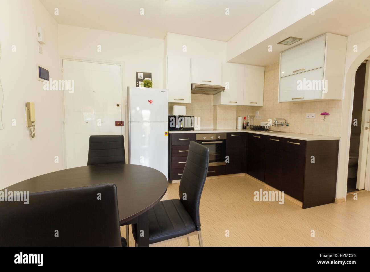 Cocina moderna en colores blanco y Wengué con mesa, sillas, electrodomésticos y bancos Imagen De Stock