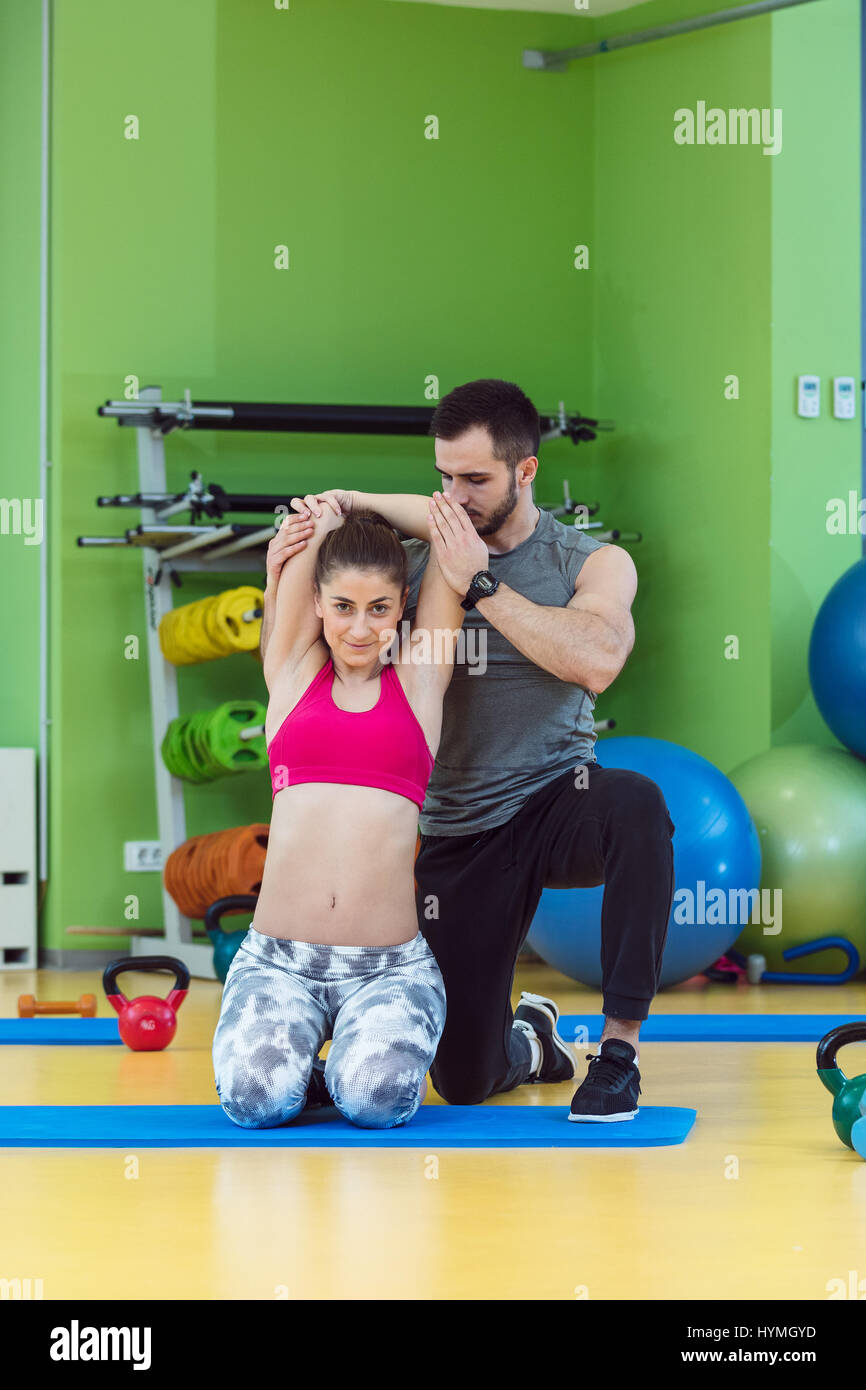 Joven que trabaja con un entrenador personal en el gimnasio. Imagen De Stock