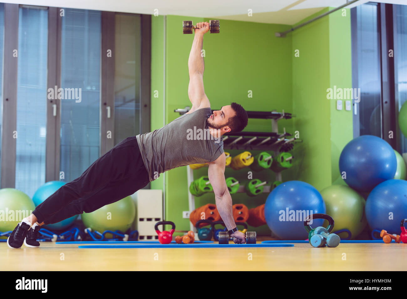 Joven levantar pesa en el gimnasio Imagen De Stock