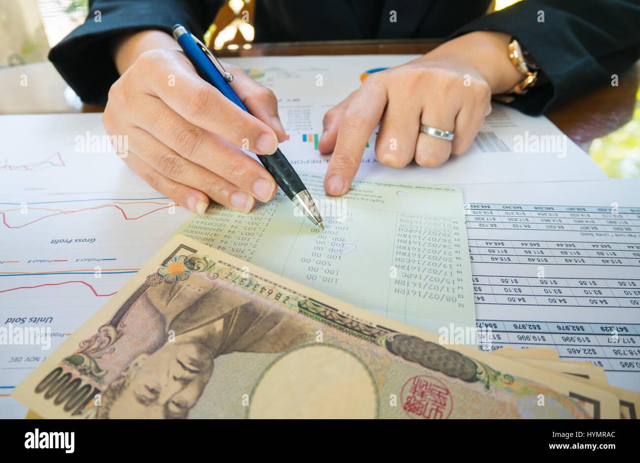 Mujer de negocios mano sostenga el lápiz y punto de declaración o informe financiero y Japón dinero en concepto Foto de stock